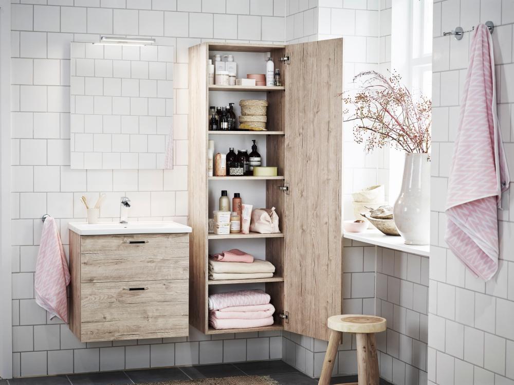 Badrumsmiljö med vitt kakel, två badrumsskåp med trälook på lådor och dörr.