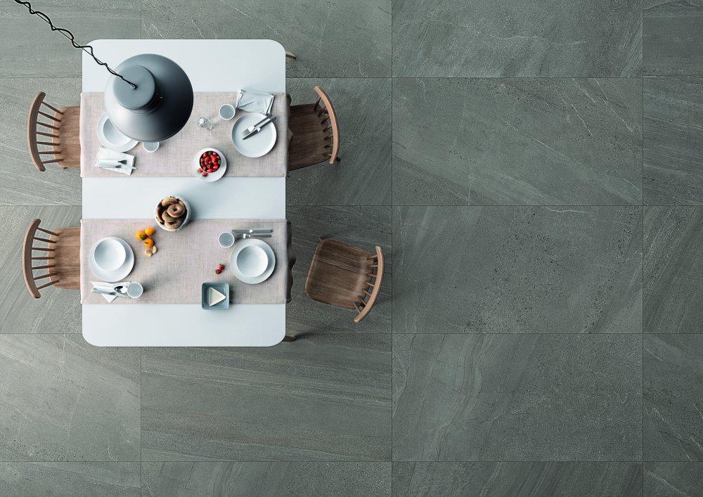 Ett matbord sett ovanifrån, på golvet ligger Nordic Stone ljust grå plattor