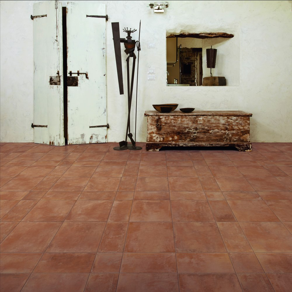 Kakeldaxgruppen-rum med cotti d'italia på golvet och vit vägg