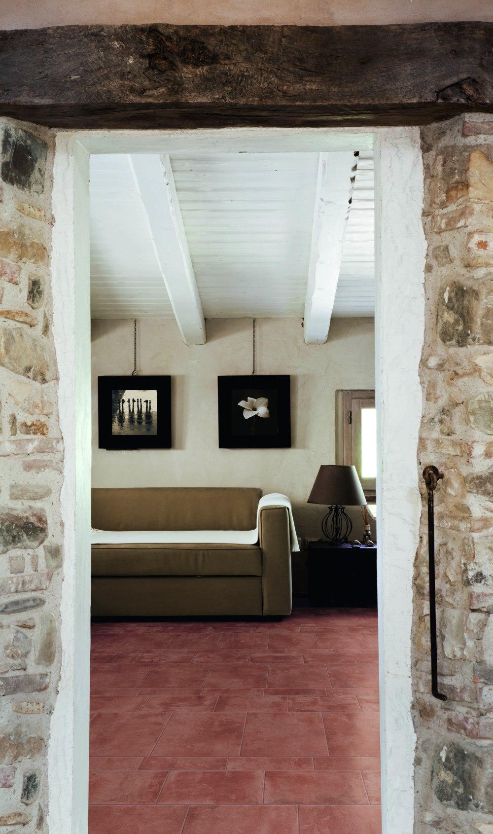Kakeldaxgruppen-vy mot vardagsrum med cotti d'italia på golvet, ljusa väggar och soffa