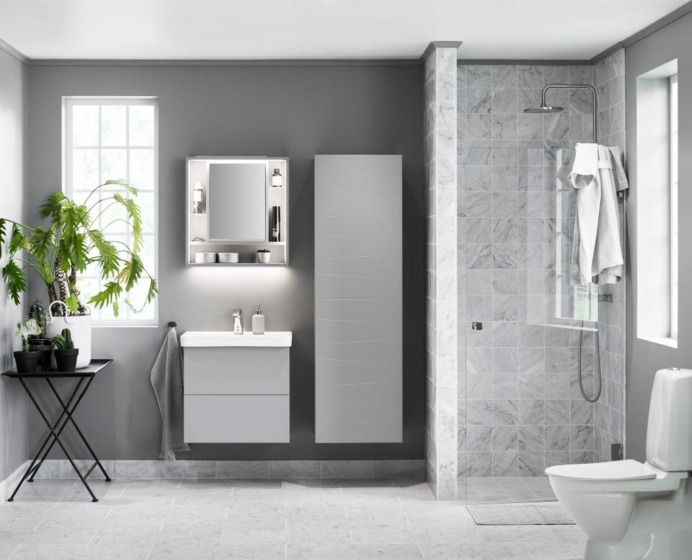 Badrum med gråa färgtoner och badrumsskåp och spegel