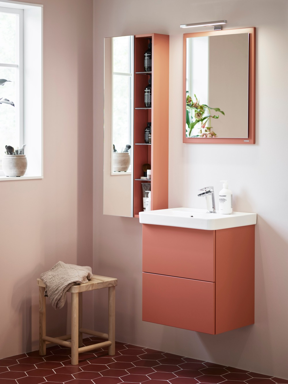 Badrumsmiljö i ljust rosa toner med badrumsskåp i färgen soft persika