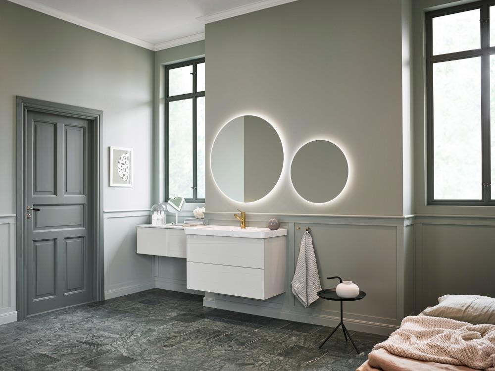 Badrumsmiljö med gröna färgtoner och tvättställ med lådor i ljusa färger samt två runda speglar