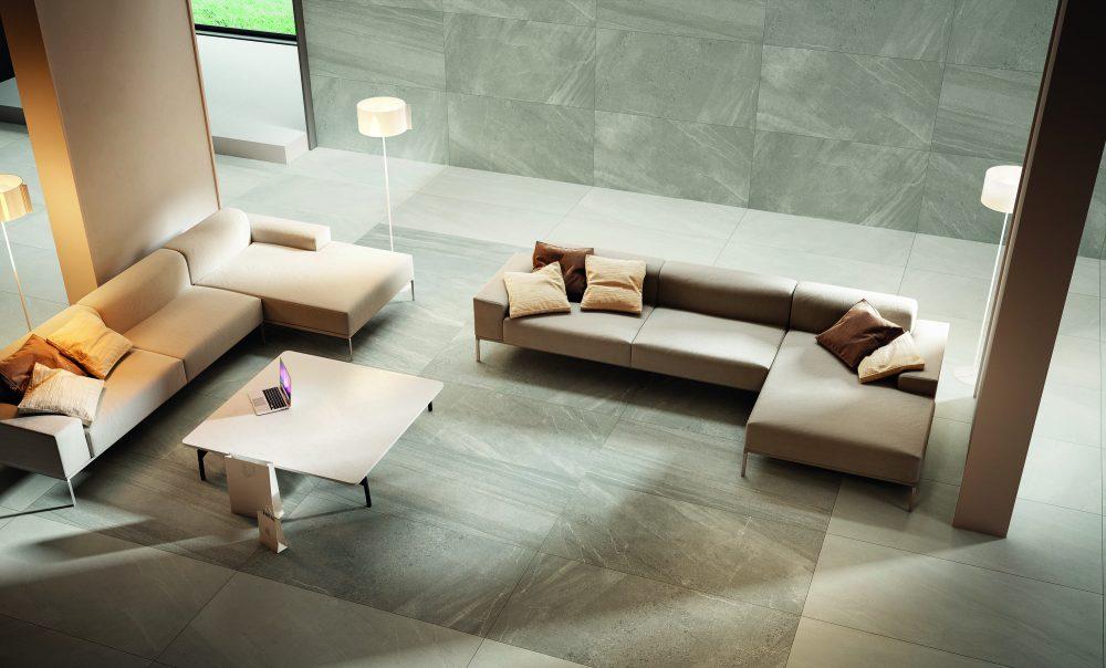 Miljöbild med en soffgrupp, på golv och vägg sitter beige platta Nordic Stone
