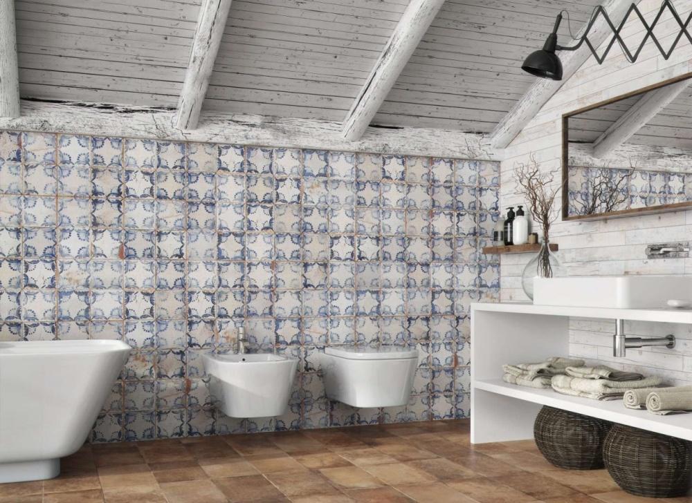Badrum med blå mönstrad platta på väggen.