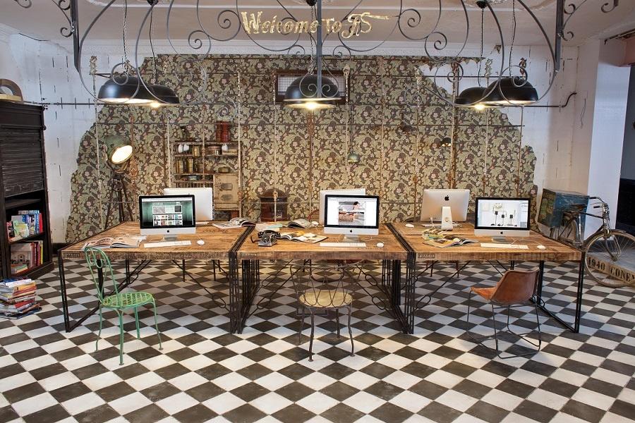 Miljöbild på rum med skrivbord med datorer. Golvet är rutigt svart och vitt.