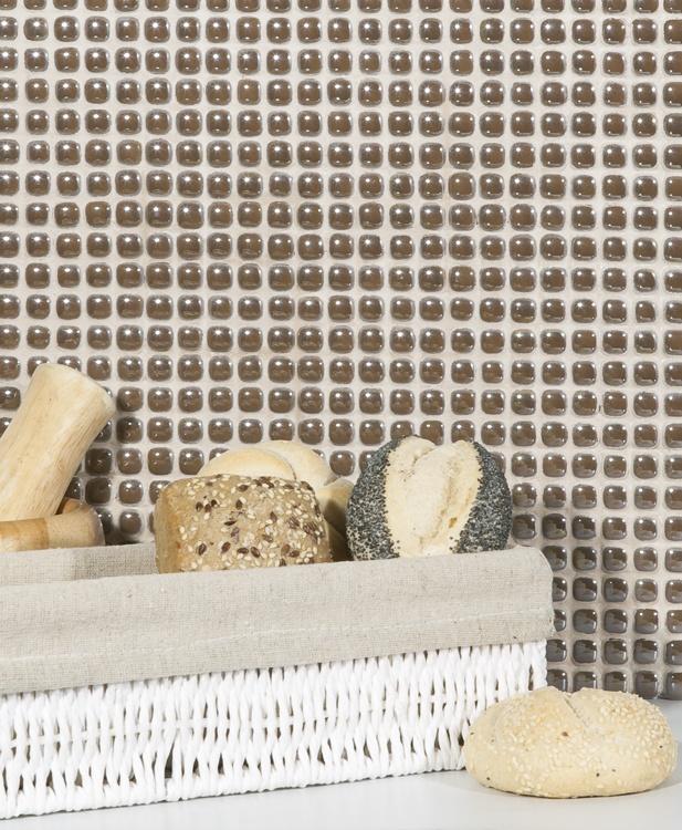Närbild på vägg med brun glasmosaik, framför väggen står en korg med bröd.
