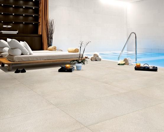 Poolutrymme inomhus med ljusa plattor på golv och vägg, en pool och två soolbäddar.