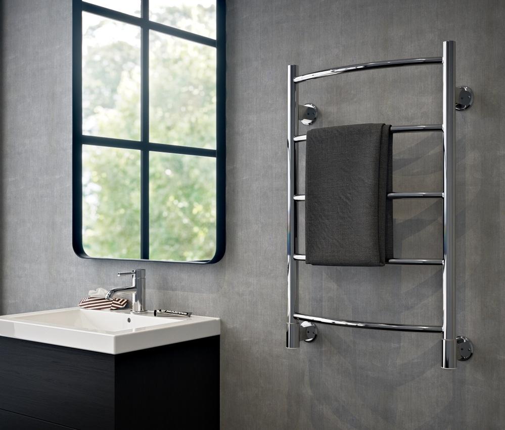 Badrum med gråa väggar och en handdukstork i metall samt tvättställ och spegel
