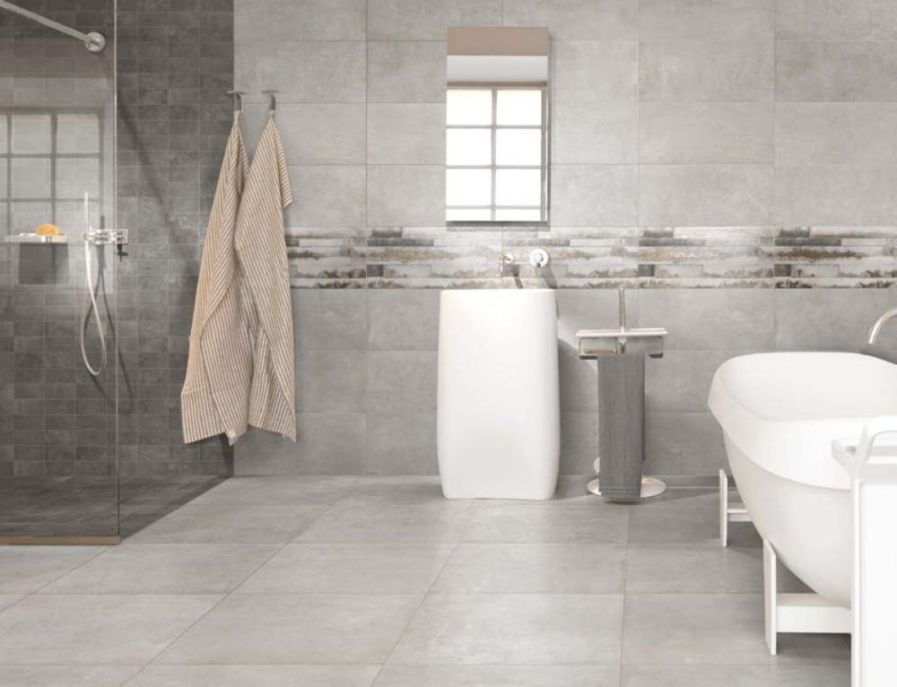 Badrum i flera nyanser av grått. I duschhörnan än det mörkt kakel och i resten av rummet ljusare.