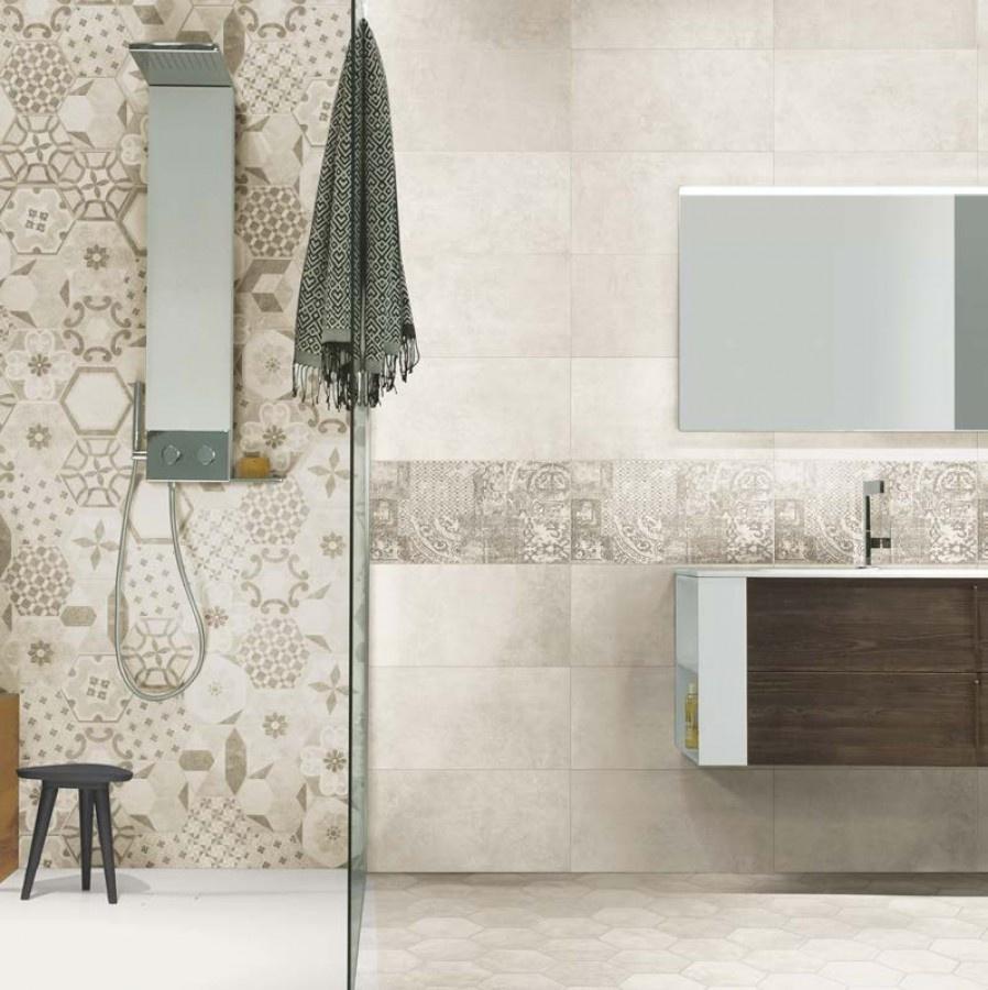 Badrum med beige plattor. Till vänster en dusch med mönstrade plattor, resten är enfärgade