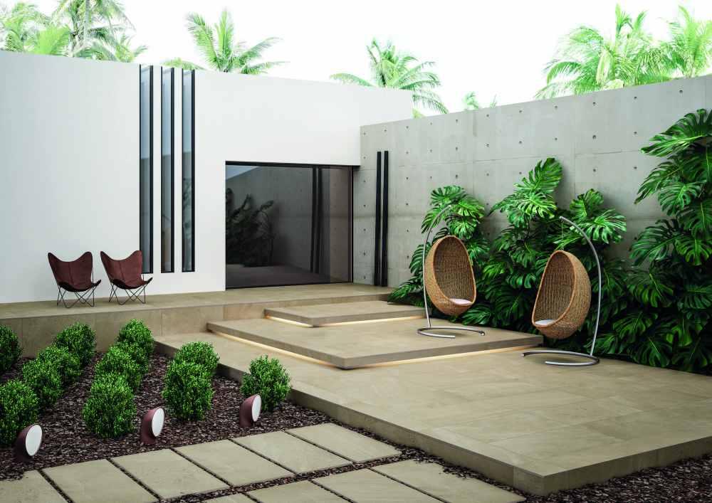 Uteplats framför hus. På uteplatsen ligger beige plattor och det finns växter och flera stolar.