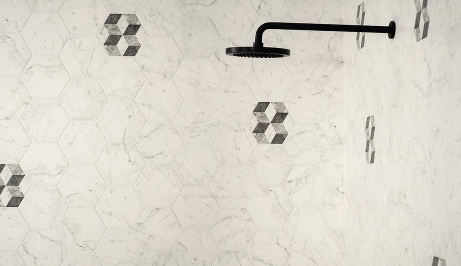 Duschutrymme med hexagonformade marmorplattor samt ett svart duschmunstycke