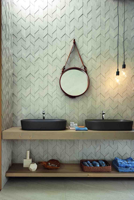 Badrum med beige 3D-mosaik på väggen, två handfat och en rund spegel.
