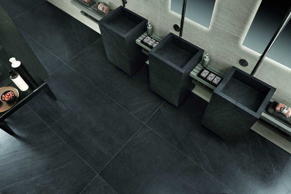 Badrum sett ovanifrån. Golvet består av mörka plattor, det finns tre handfat och väggarna är ljusa.