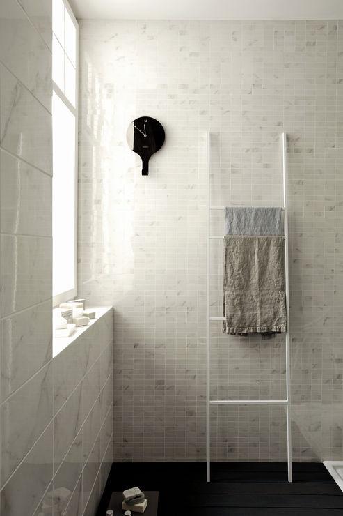 Badrumsmiljö med ljusa plattor på väggarna.