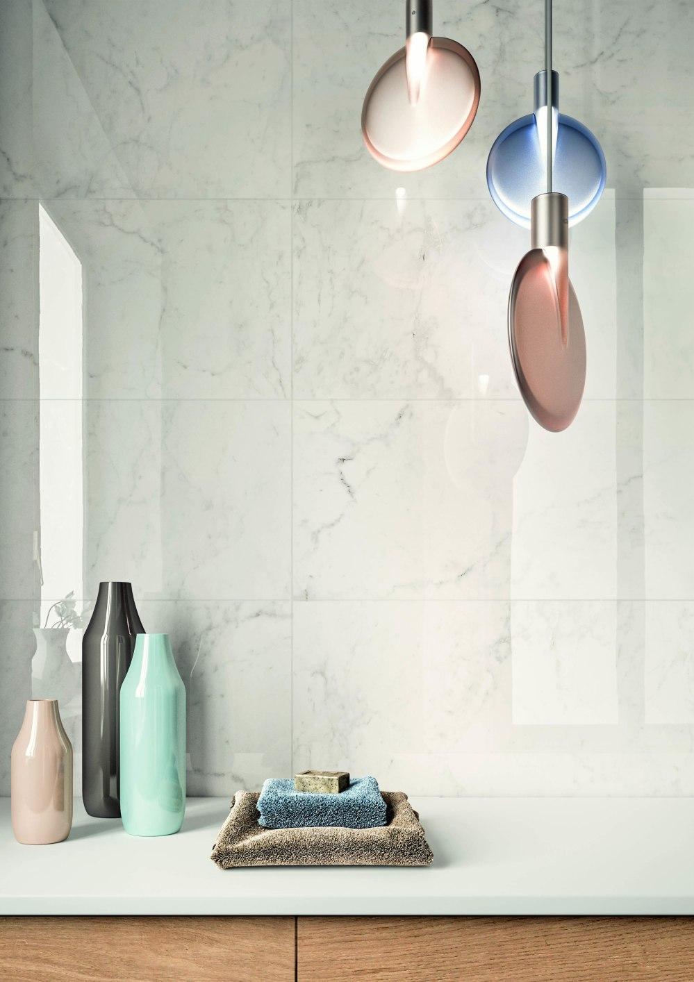 Miljöbild från badrum. På väggen sitter en blank marmorliknande platta. På en skänk ligger handdukar och en tvål.