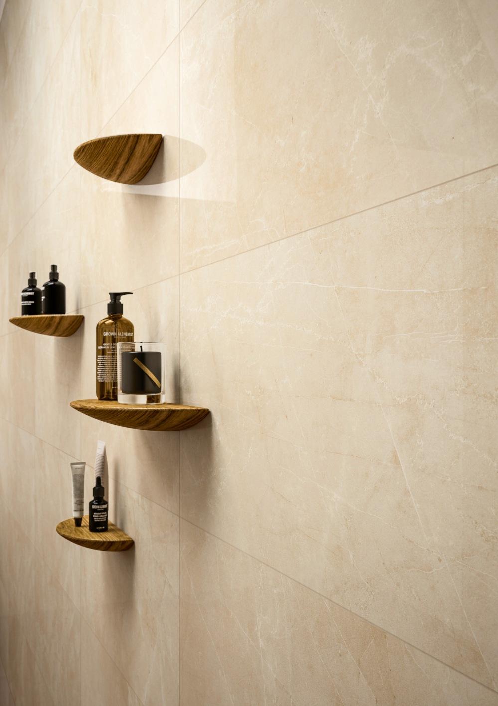 Vägg i badrum med beige marmorplatta. På väggen sitter också små hyllor med tvålpump och liknande.