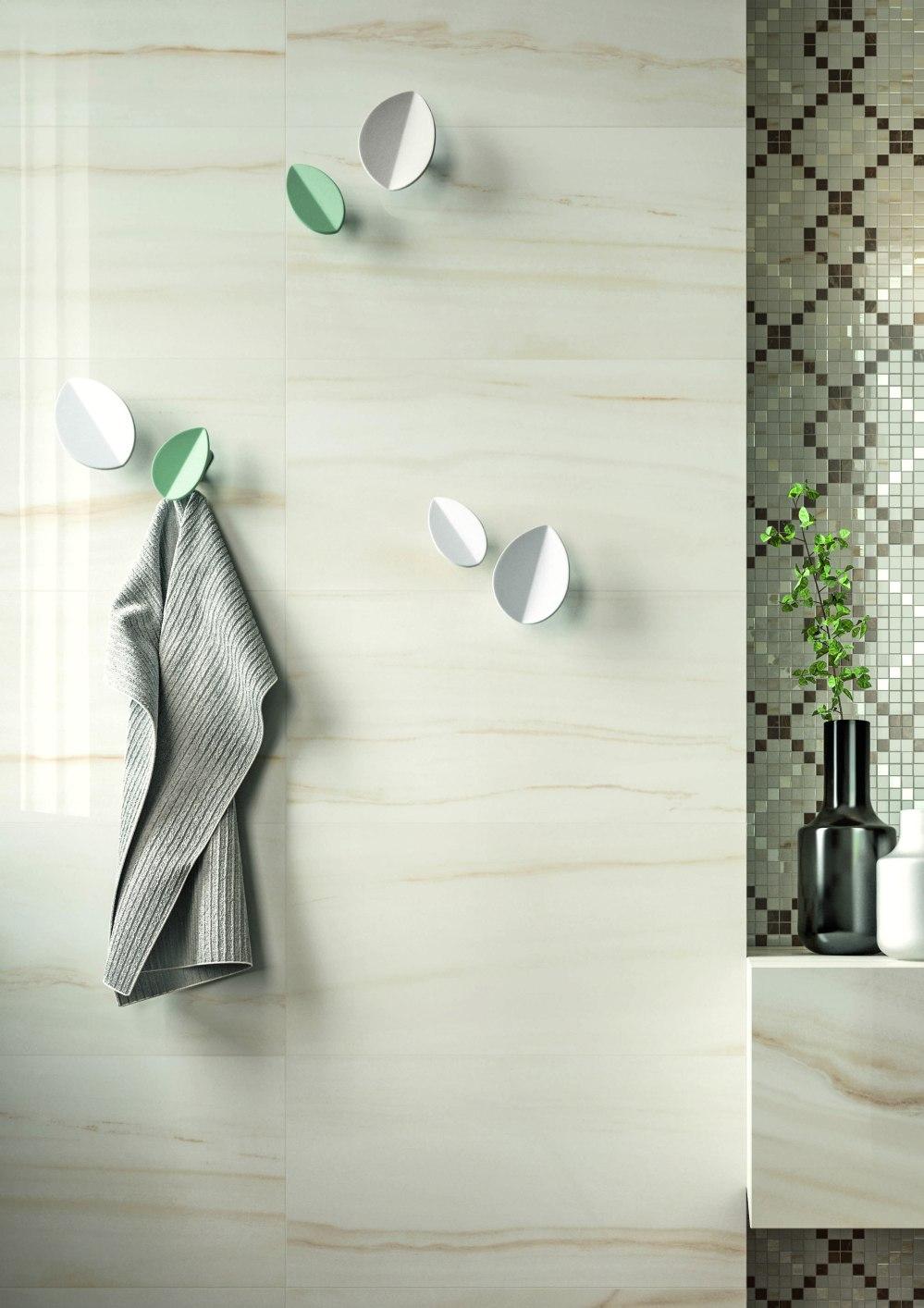 Miljöbild från badrum. På väggen en ljusbeige marmorplatta och handdukskrokar med en handduk.