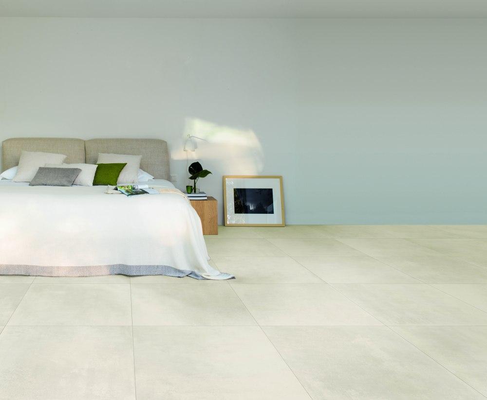 Miljöbild på sovrum med en säng med vitt överkast. På golvet ligger ljusa, cementliknande plattor