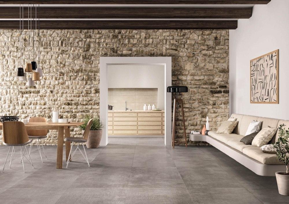 Miljöbild på rum med matsalsbord och soffa. På golvet ligger en beige-grå cementliknande platta.