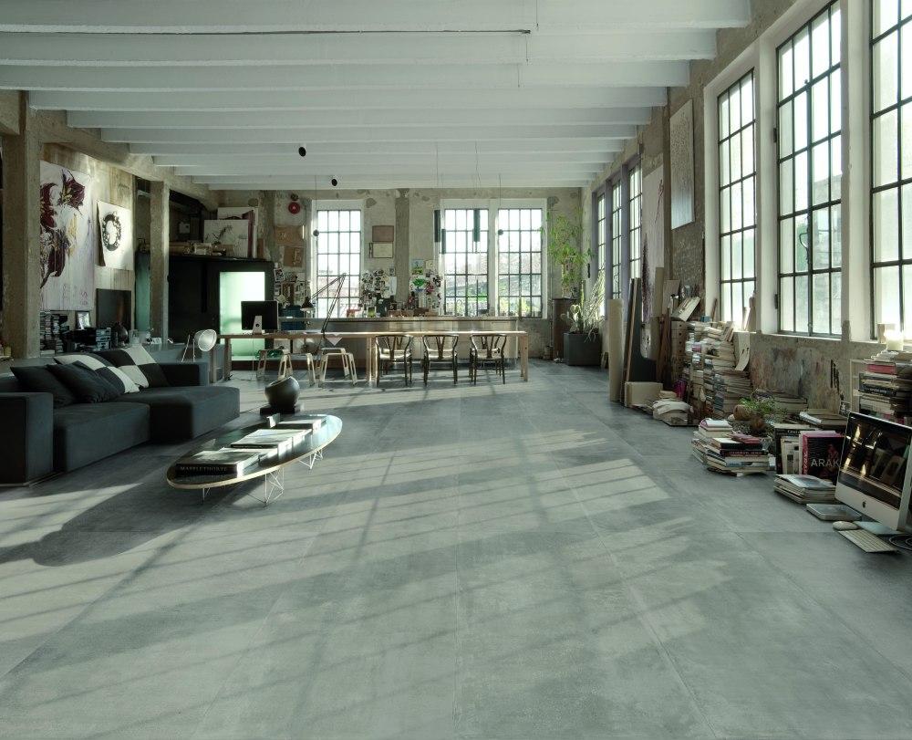 Miljöbild över rum med industriell stil. På golvet ligger stora, gråa betonglinknande plattor