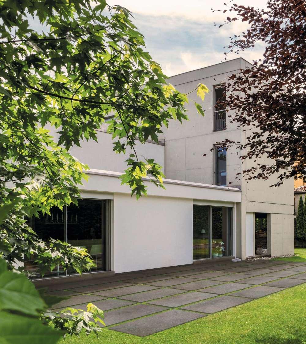 Exteriör bild på hus. På gräsmattan framför huset ligger stora, mörkgråa plattor för utomhusbruk.