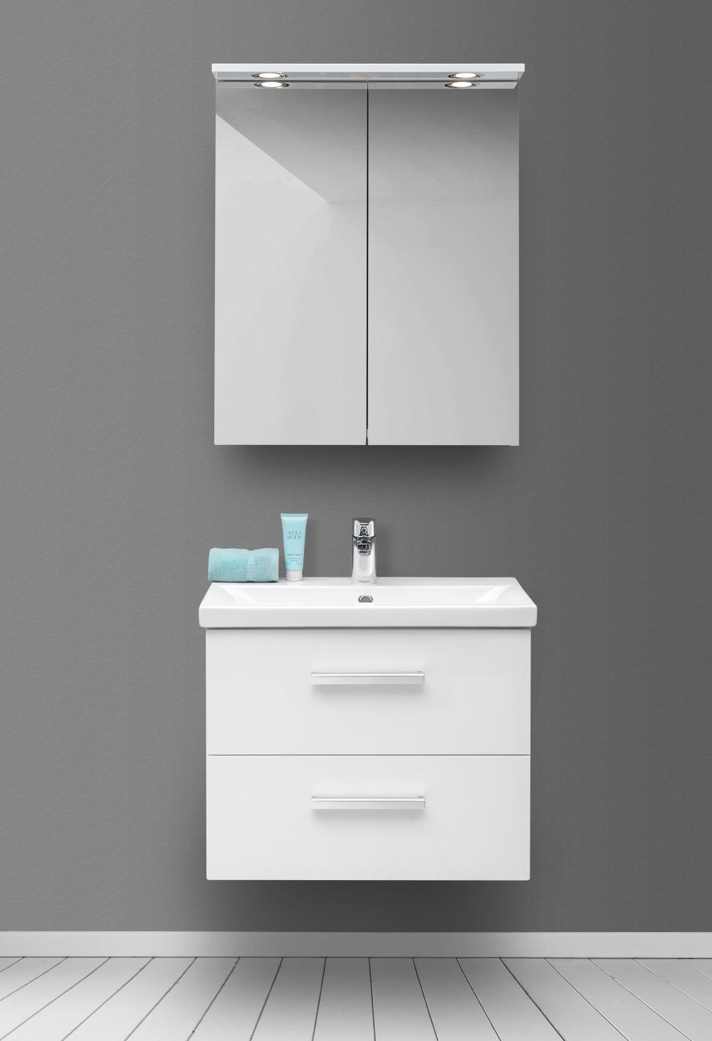 Bild tagen framifrån som visar badrumsmöbler i form av ett vitt underskåp med två lådor och tvättställ. Ovanför sitter ett spegelskåp med två dörrar.