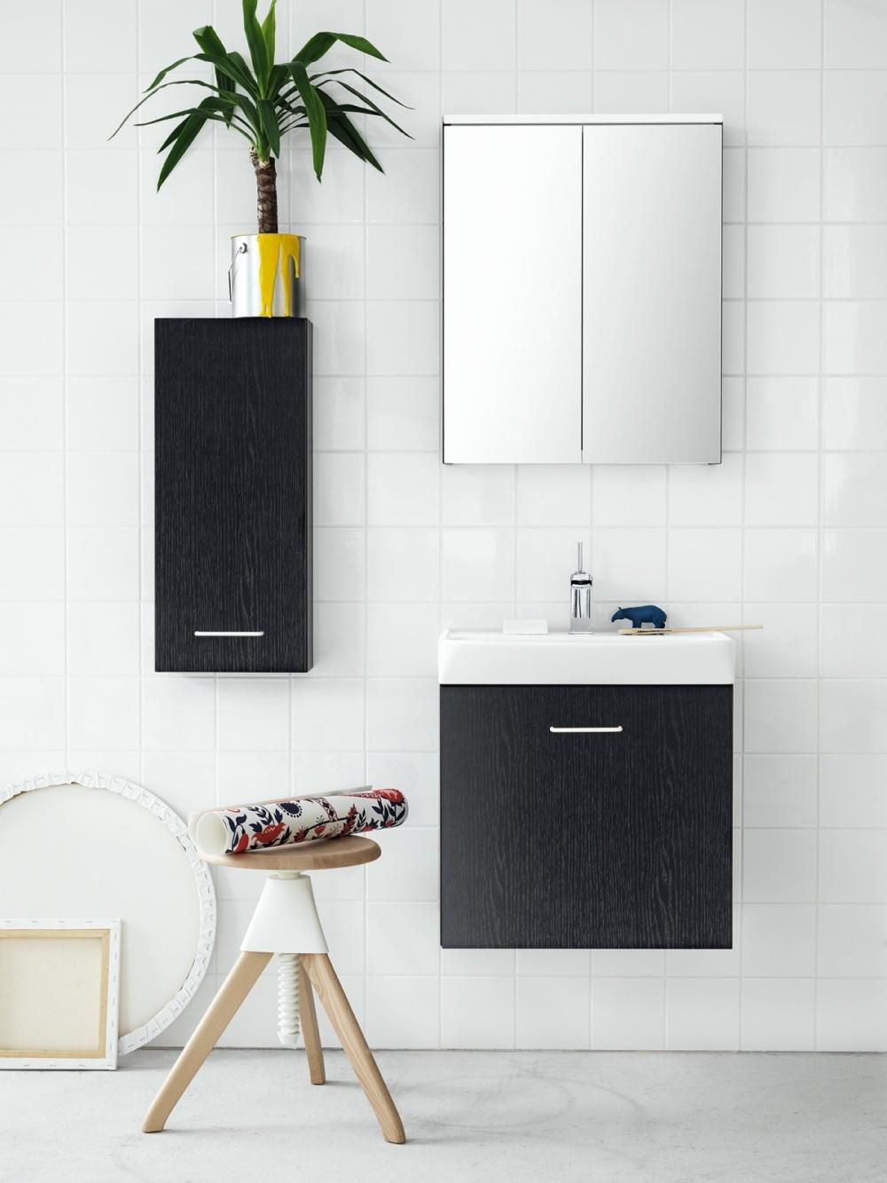 Bild tagen framifrån på badrumsmöbler. Ett svart badrumsskåp med tvättställ och en låda. Ovanför sitter ett spegelskåp med två dörrar och till vänster ett vägghängt svart skåp.