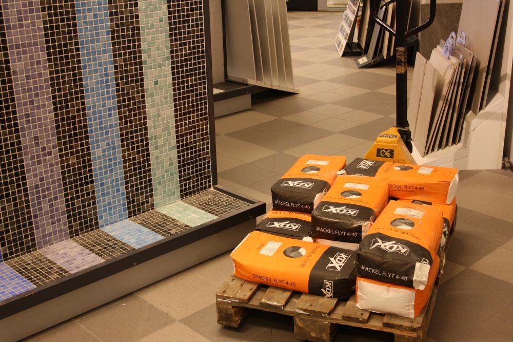 Bild på lastpall med flera orange säckar med texten KDX Spackel Flyt