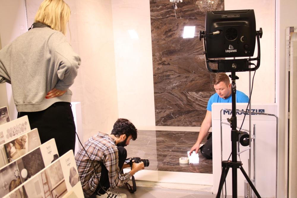 Överblicksbild över badrumsmiljön. Tre personer syns, en kvinna som står upp, en man som sitter på huk och fotograferar samt en som sitter på knä och arbetar med kaklet.
