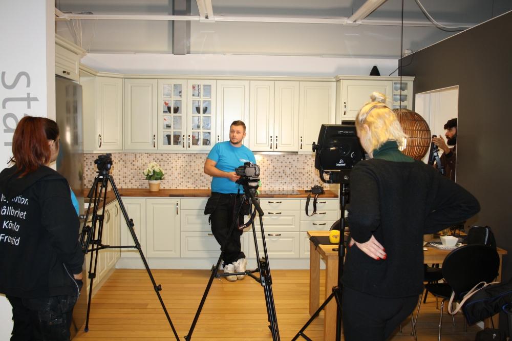 Vy över ett visningskök. I förgrunden står filmkameror på stativ och i köket står en man som är plattsättare.