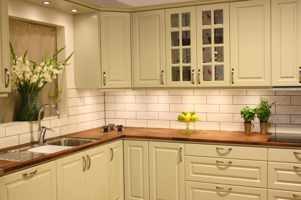 Översiktsbild på ett kök med ljust gröna köksluckor och bänkskiva i trä. Väggen har vitt rektangulärt kakel.