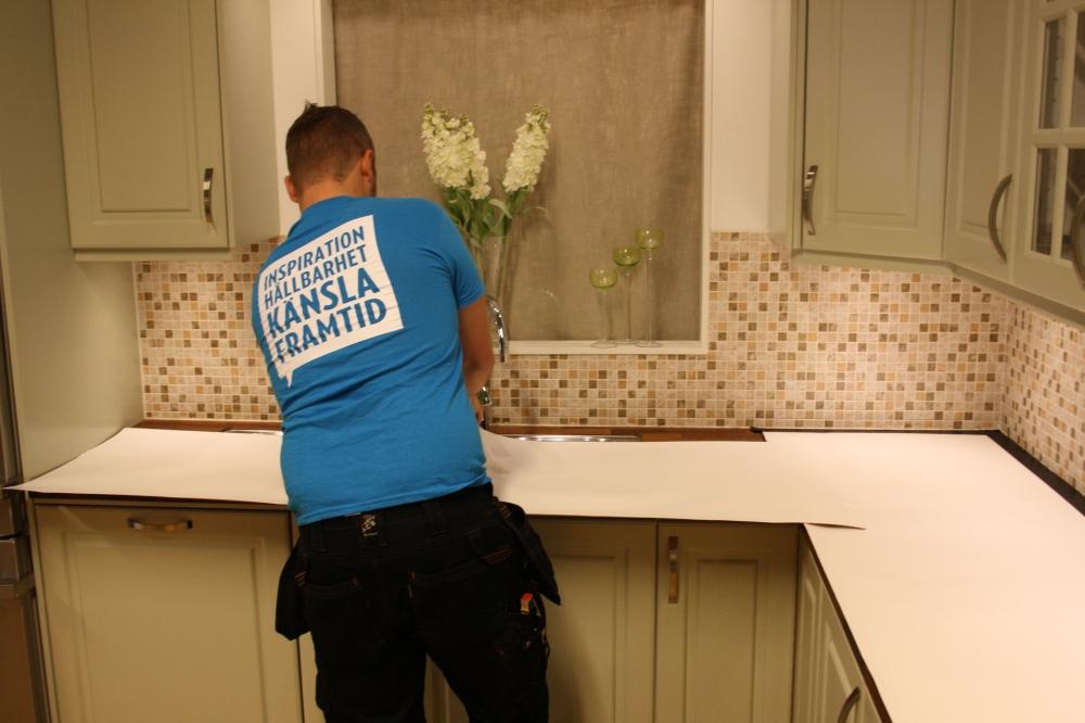En man står med ryggen mot kameran. Han täcker en bänkskiva i ett kök med papp.