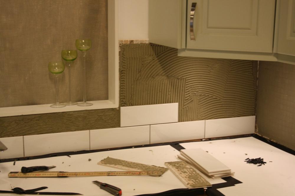 Bild på en yta över bänkskiva i kök. Väggen är täckt med fix och en rad vitt kakel har satts närmast bänkskivan.