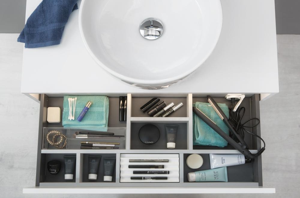 Bild på låda i badrumsskåp tagen ovanifrån. I lådan finns ett system av fack för krämer, smink och annat.