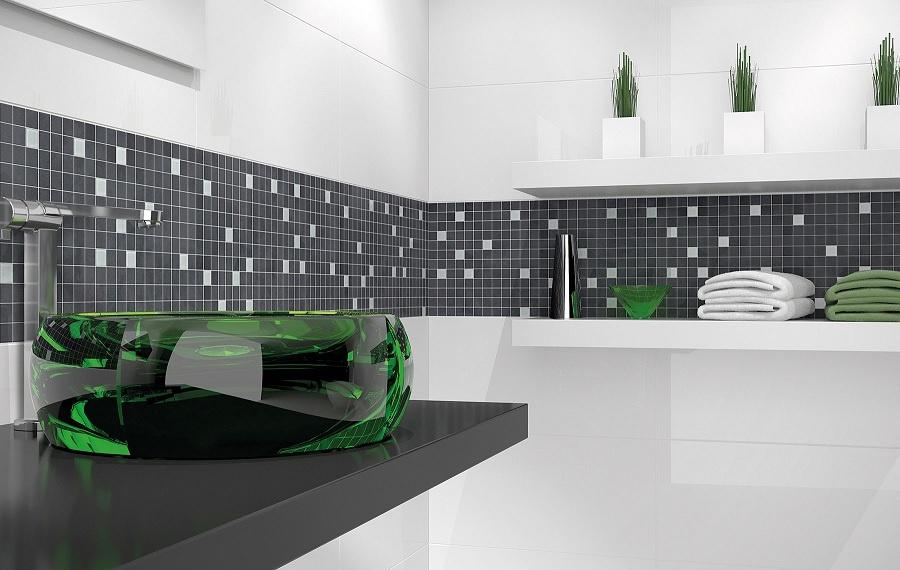 Miljöbild över ett badrum. Väggarna är vita och har en rand av mosaik.
