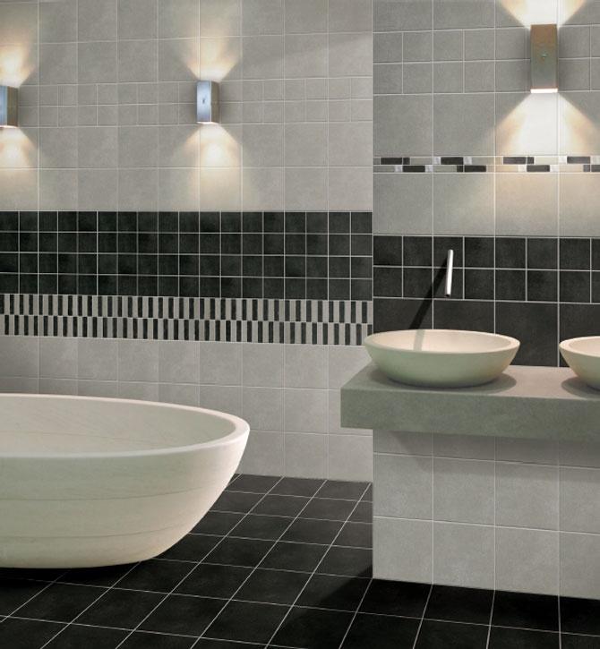 Badrum med svart golv och vita väggar med svart bård. Det finns även ett badkar och handfat.