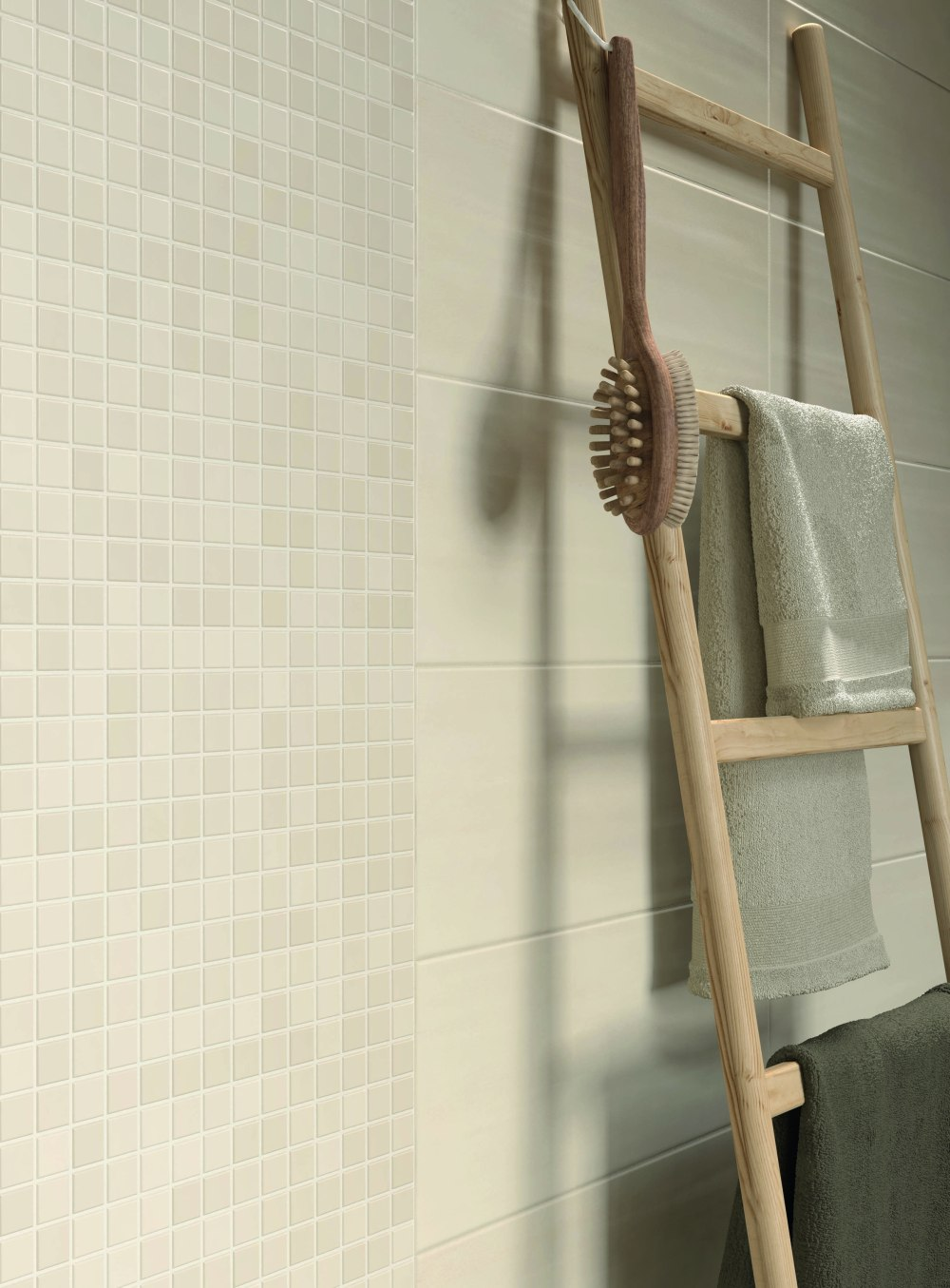 Bild på badrumsvägg med beige mosaik och kakel.