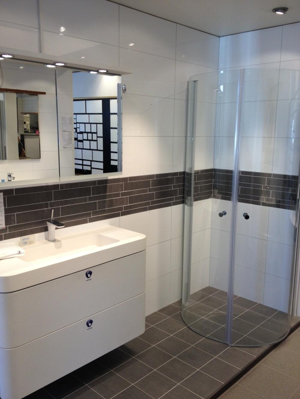 Miljöbild över badrum med vitt kakel på väggar och grått kakel på golv. Mitt på väggen går en bård av grå mosaik.