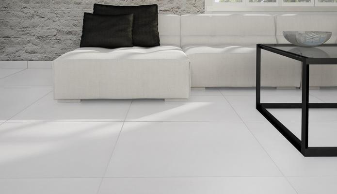 Bild från vardagsrum. Det mesta i bilden går i vitt, soffan, väggen och plattorna på golvet.