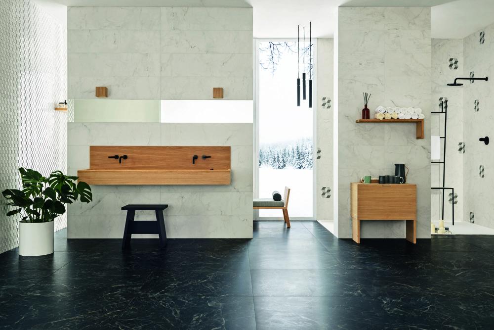 Miljöbild över badrum med ljusa marmorplattor på väggarna och mörka marmorplattor på golvet. Badrumsmöblerna är i trä.