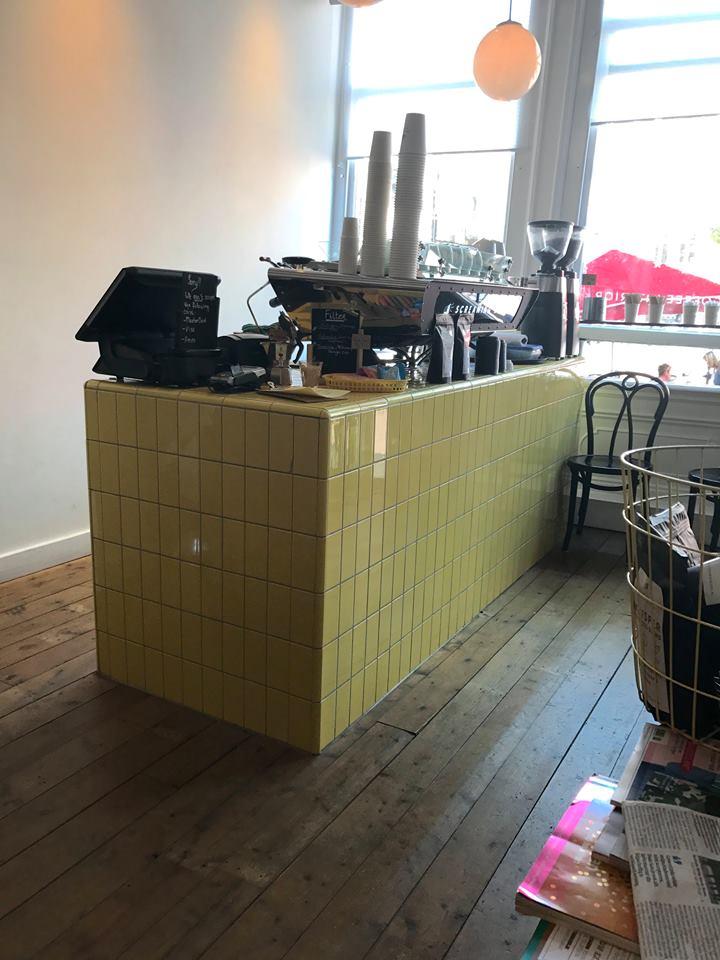 Bild tagen på ett café. Golvet är av trä och det finns en disk med kasse och kaffemaskin klädd i gult kakel.
