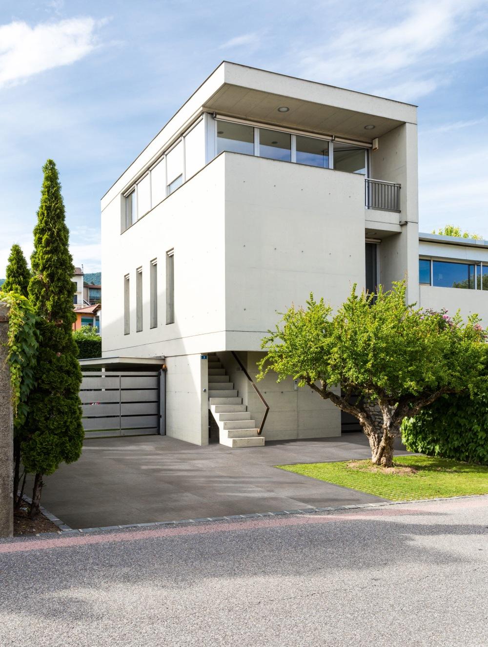 Bild tagen utomhus. Bilden visar ett vitt hus i modern stil med ett garage. På garageuppfarten ligger grå storformatsplattor.