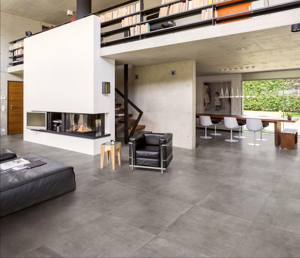 Miljöbild över vardagsrum och matsal. Genomgående används en grå platta på golvet.