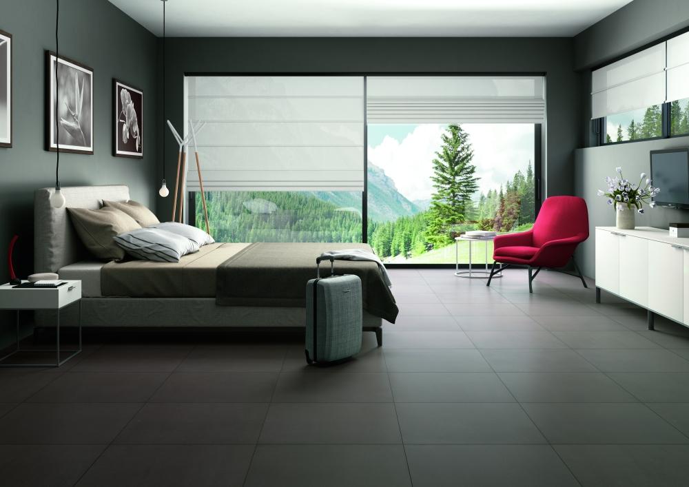 Bild över ett sovrum med en stor säng och stora fönster genom vilka naturen syns. Bilderna går i brunt och på golvet ligger bruna plattor i storformat.