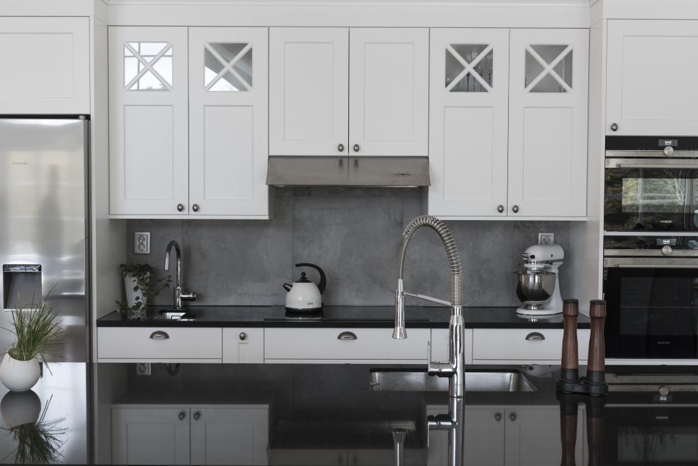 Miljöbild på kök med vita skåpsluckor, svart bänkskiva och mörkgråa plattor på väggen över bänkskivan.