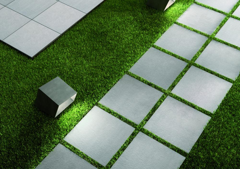 Bild på kvadratiska plattor med stenlook som ligger på en gräsmatta.