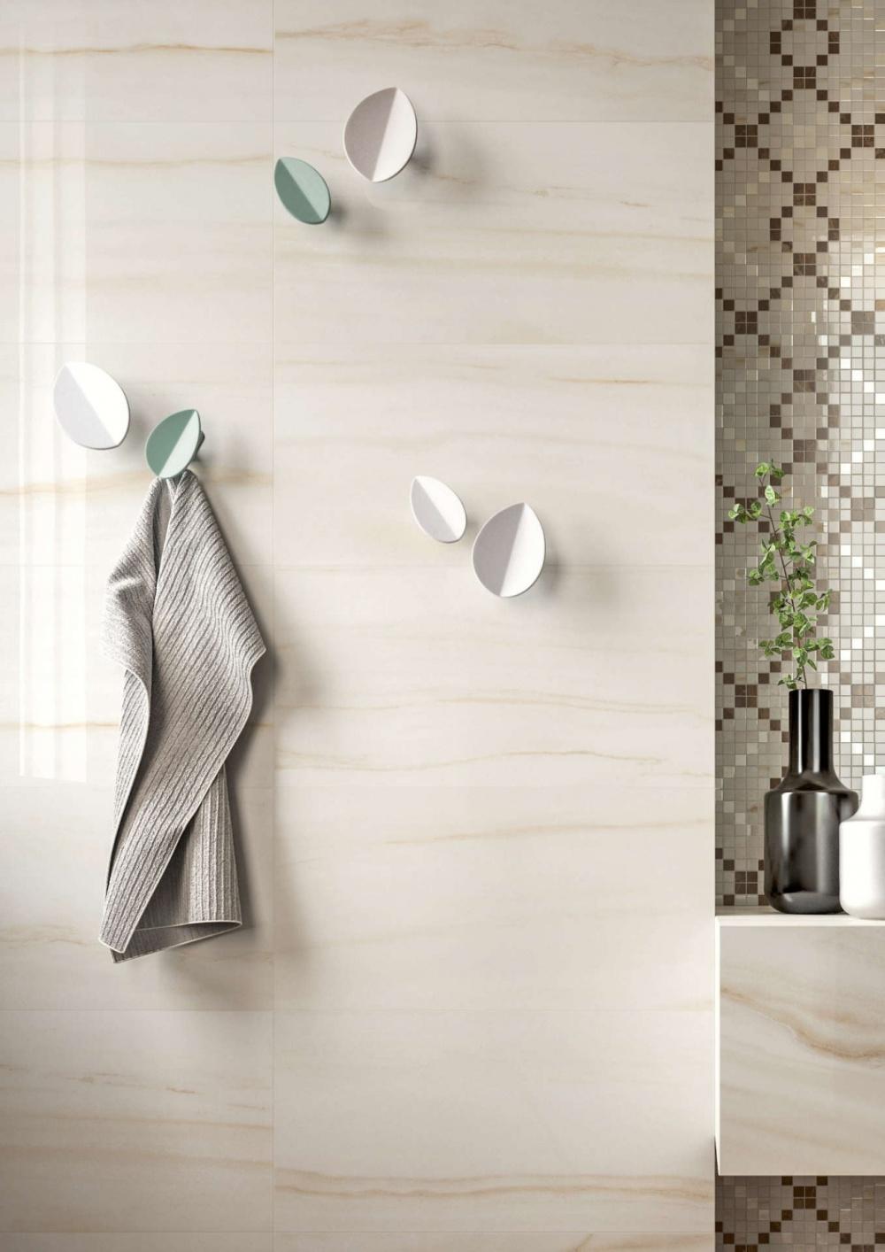 Bild på vägg i badrum som har marmorliknande platta i beige. På väggen sitter sex handdukshängare.