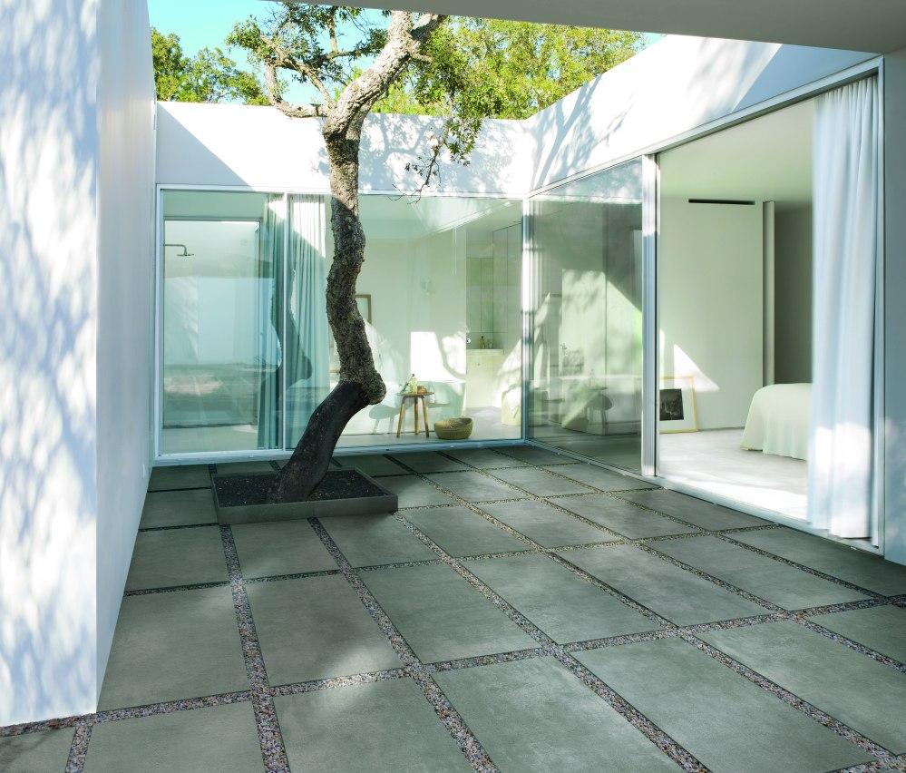 Miljöbild utomhus. Ett vitt hus med stora glaspartier. På marken finns 20 mm-plattor lagda direkt på grus.